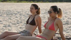 Mädchen zwei, das auf dem Strand ein Sonnenbad nimmt und spricht stock video