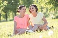 Mädchen zwei, das auf Gras lacht Stockbild