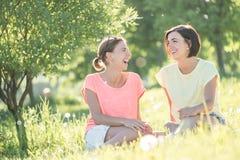Mädchen zwei, das auf Gras lacht Stockbilder