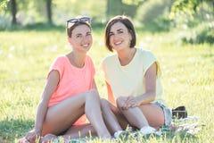Mädchen zwei, das auf Gras lacht Lizenzfreies Stockbild