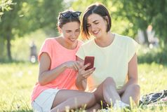 Mädchen zwei, das auf Gras lacht Lizenzfreie Stockbilder