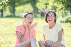 Mädchen zwei, das auf Gras lacht Stockfotografie