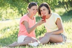 Mädchen zwei, das auf Gras lacht Stockfotos