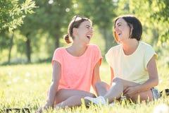 Mädchen zwei, das auf Gras lacht Lizenzfreies Stockfoto