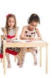 Mädchen zwei, das bei Tisch zeichnet Lizenzfreie Stockbilder