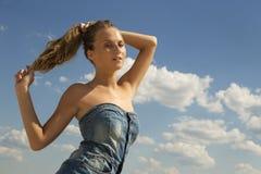 Mädchenabgehobener betrag zurück ihr Haar in einen Pferdeschwanz über blauem Himmel Stockfotos