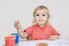 Mädchenanstrich mit einem Pinsel Stockbilder