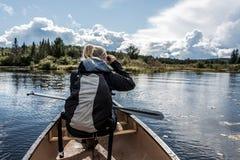 Mädchenanwendung binokular auf Canoe See von zwei Flüssen im Nationalpark des Algonquin in Ontario Kanada am sonnigen bewölkten T Lizenzfreie Stockbilder