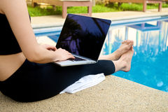 Mädchenarbeit mit Laptop am Pool Stockfotos