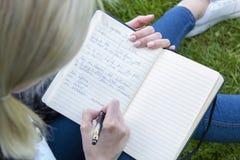 Mädchenarbeiten schreibt Informationen in ein Notizbuch stockfotografie