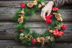 Mädchenarm, der roten Bogen trägt und rustikale Blockhauswand mit Weihnachtskranz verziert Lizenzfreie Stockbilder