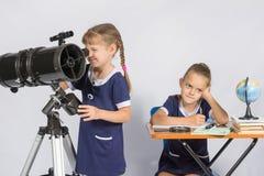 Mädchenastronom schaut durch das Okular des Teleskops, das andere Mädchen, das auf die Ergebnisse der Beobachtungen wartend denkt Lizenzfreie Stockfotografie