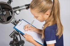 Mädchenastronom schreibt auf ein Blatt Papier eines sternenklaren Himmels mit Ihrem Teleskop Stockfoto