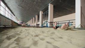 Mädchenathlet, der zuhause Weitsprung in den Sandkasten durchführt stock video