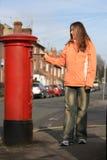 Mädchenaufgabezeichen zum roten britischen Postbox Lizenzfreies Stockbild