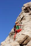 Mädchenaufstiege auf einem Felsen Lizenzfreies Stockfoto