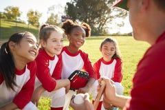 MädchenBaseballteam in einem Teamwirrwarr mit dem Trainer, hörend stockfotografie