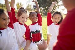 MädchenBaseballteam in einem Wirrwarr mit dem Trainer, Hände anhebend stockbild