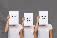 Mädchenbedeckungsgesicht mit weißen Brettern Satz gemalte Gefühle Stockfotografie