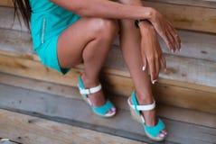 Mädchenbeine im Türkiskurzschlusskleid, das auf einem Baumklotz sitzt lizenzfreie stockbilder