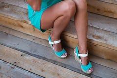 Mädchenbeine im Türkiskurzschlusskleid, das auf einem Baumklotz sitzt lizenzfreie stockfotografie