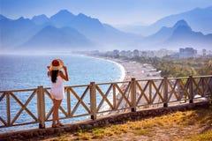 Mädchenbetrachtungstürkis Antalya setzt von einer Terrasse auf den Strand stockfoto