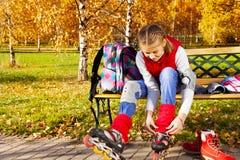 Mädchenbindungsspitzee auf Rollerblades Stockfotografie