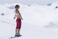 Mädchenblondine in den schneebedeckten Bergen hoch über den Wolken Stockfotografie