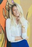 Mädchenblondine mit dem langen Haar, gegen Wandgraffiti stockfotografie