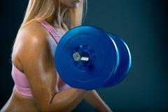 Mädchenbodybuilder auf einem Hintergrund des blauen Graus mit großem Dummkopf in den Händen Lizenzfreies Stockbild