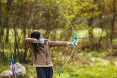 Mädchenbogenschützeschießen mit seinem Bogen lizenzfreie stockfotos