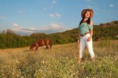 Mädchencowboy, der auf einem Gebiet mit einem Pferd steht lizenzfreie stockfotografie