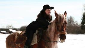 Mädchencowboy, der auf einem Pferd sitzt Lizenzfreie Stockfotos