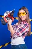 Mädchenerbauer im Bausturzhelm und Schutzbrillen mit einem Bauwerkzeug auf einem blauen Hintergrund Lizenzfreies Stockbild