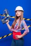Mädchenerbauer im Bausturzhelm und Schutzbrillen mit einem Bauwerkzeug auf einem blauen Hintergrund Lizenzfreie Stockfotos