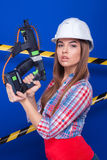 Mädchenerbauer im Bausturzhelm und Schutzbrillen mit einem Bauwerkzeug auf einem blauen Hintergrund Lizenzfreie Stockfotografie