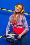 Mädchenerbauer im Bausturzhelm und Schutzbrillen mit einem Bauwerkzeug auf einem blauen Hintergrund Stockfoto