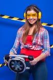 Mädchenerbauer im Bausturzhelm und Schutzbrillen mit einem Bauwerkzeug auf einem blauen Hintergrund Stockbild
