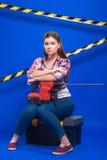 Mädchenerbauer im Bausturzhelm und Schutzbrillen mit einem Bauwerkzeug auf einem blauen Hintergrund Stockfotos