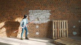Mädchenerbauer, mit dem dunklen Haar, Farbenrollenbacksteinmauer stock video footage