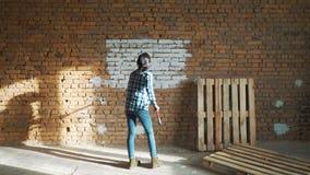 Mädchenerbauer, mit dem dunklen Haar, Farbenrollenbacksteinmauer stock footage