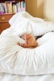 Mädchenfüße, die auf weißem Kissen am Schlafzimmer liegen Stockfoto