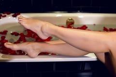 Mädchenfüße, die am Rand der weißen Wannen stehen Stockfotos