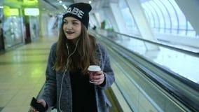 Mädchenfahrten auf travelators und Getränkkaffee stock video footage