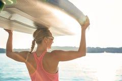 Mädchenfamilienvaterfrau tun Yoga auf einem Sup lizenzfreies stockbild