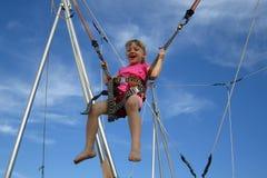 Mädchenfederelement, das auf eine Trampoline springt Stockfotografie