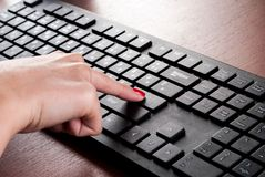 Mädchenfingerstoß kommen Knopf auf Computertastatur auf hölzernem Schreibtisch stockfotografie
