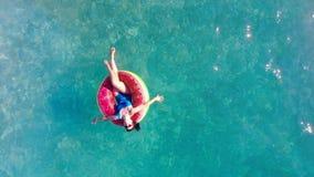 Mädchenflöße in einem Pool auf einem Gummiring stock video footage