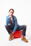 Mädchenfrau in einem blauen Hemd und in Jeans, die auf dem Ball sitzen Stockfotografie