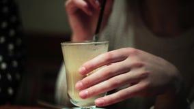 Mädchenfrau trinkt frappuchino Kälte durch ein Stroh stock footage